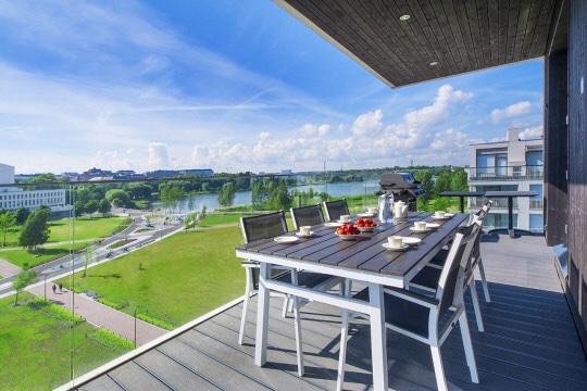 Kuvassa asunnon terassi, pöytä ja näkymä Töölönlahdelle.